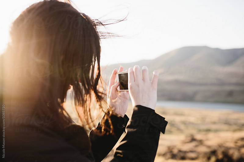woman taking photo with phone at sunset in mountain landscape by Nicole Mason for Stocksy United