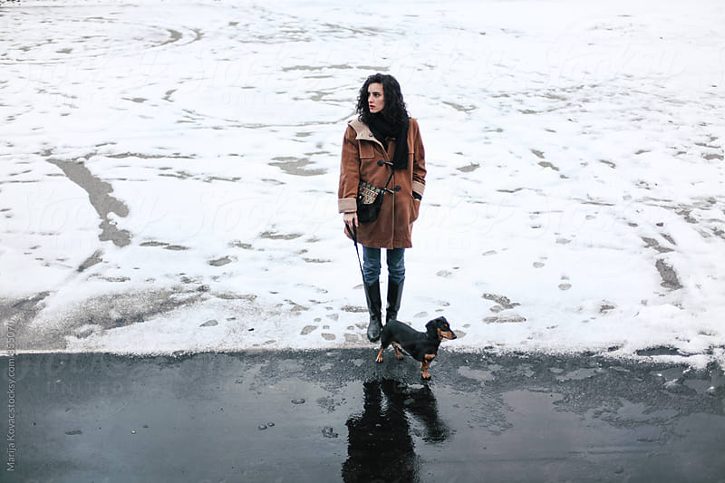 Woman and her little dog, snow  by Marija Kovac for Stocksy United