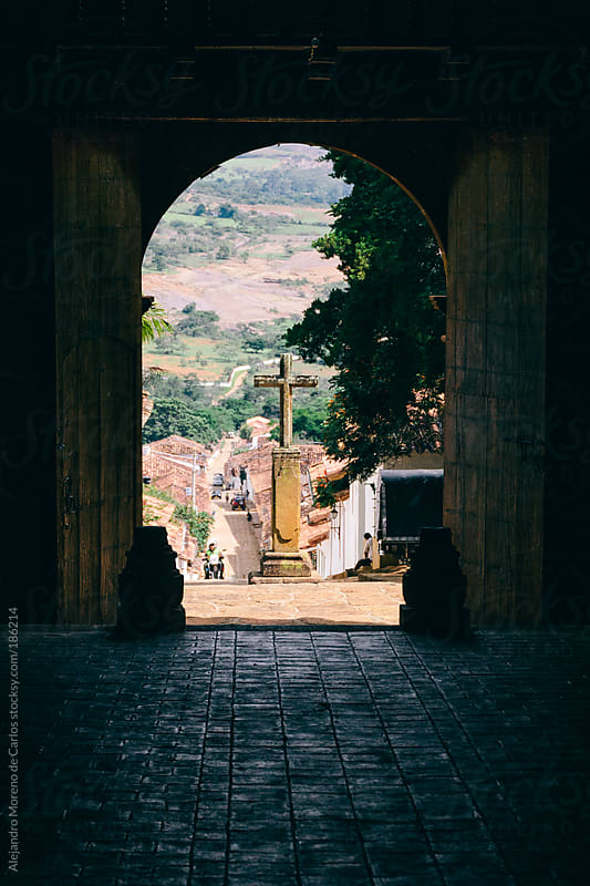 Cross seen through an arch on a traditional village by Alejandro Moreno de Carlos for Stocksy United