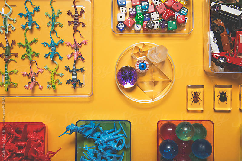 Toys arranged on yellow background... by Catherine MacBride for Stocksy United