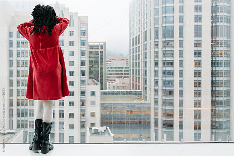 Black girl in red dress looking out of an high-rise building by Gabriel (Gabi) Bucataru for Stocksy United