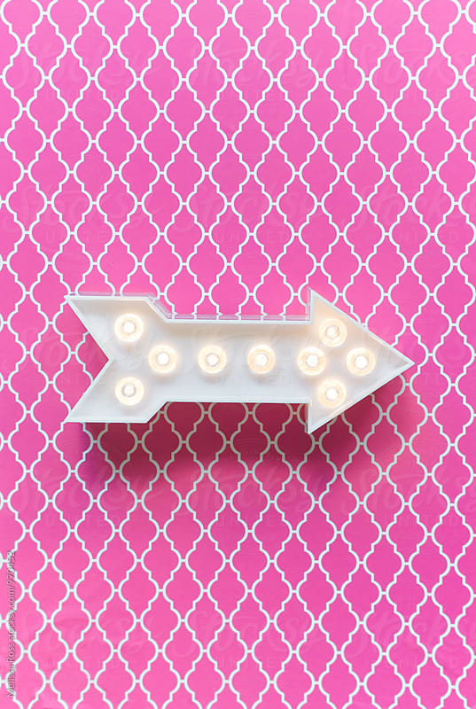 Arrow marquee light on a pink background. by Melissa Ross for Stocksy United