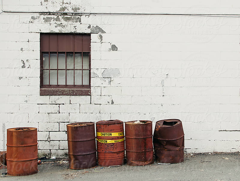 Rusty oil drums by a brick wall by Deirdre Malfatto for Stocksy United