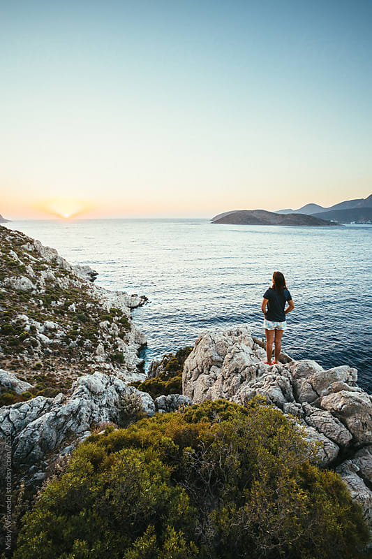 woman standing on a rocky outcrop overlooking the sea by Micky Wiswedel for Stocksy United