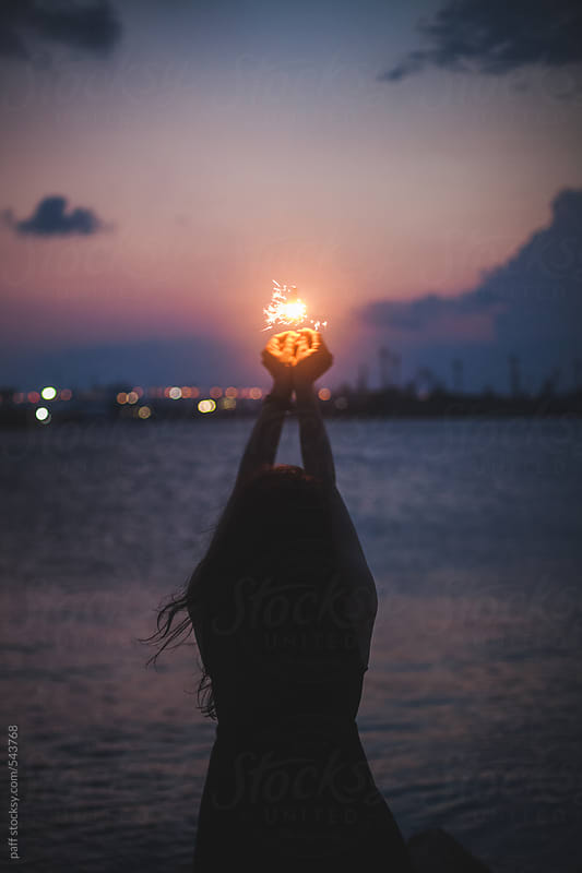 Back of a young woman holding up high a sparklers on seashore by paff for Stocksy United