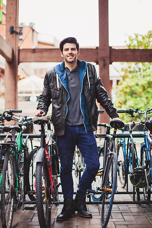 A good looking young man stands at a full bike rack. by Cherish Bryck for Stocksy United