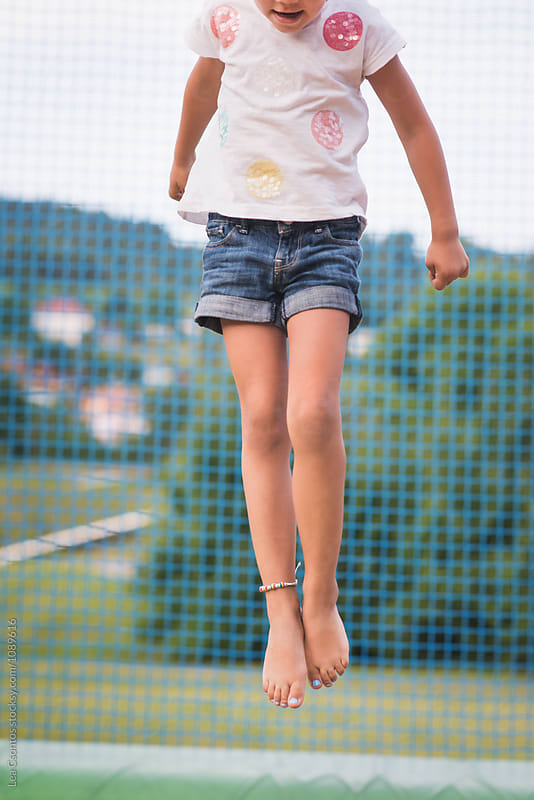 Little girl in the air, jumping on a trampoline by Lea Csontos for Stocksy United