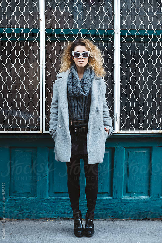 Pretty Young Woman With Curly Hair Standing In Front of the Blue Shop by Katarina Radovic for Stocksy United