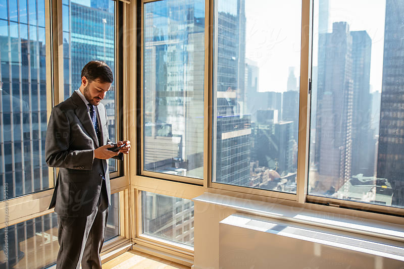 Young businessman checking his phone in an office with the view of the city in the background by Inuk Studio for Stocksy United