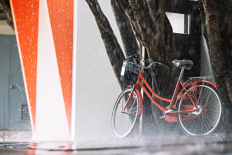 Lone orange bike parked and unused because of the pouring rain by Lawrence del Mundo for Stocksy United