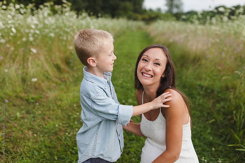 Mother and son in a field, mom looking at camera by Amanda Worrall for Stocksy United