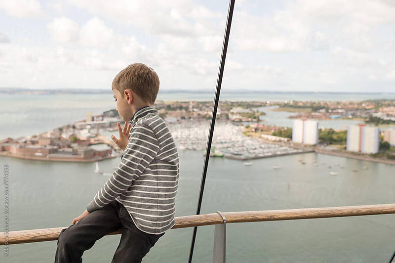 Boy watches the harbour below through a glass observation platform window by Rebecca Spencer for Stocksy United