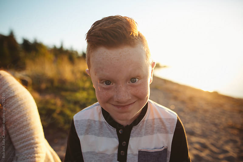 Funny freckled boy making face toward camera by Rob and Julia Campbell for Stocksy United