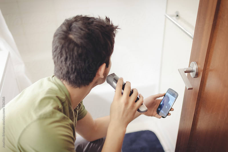 Young Mexican-American Man Shaving Using Smartphone Camera App as Mirror by Joselito Briones for Stocksy United