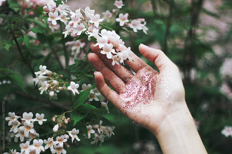 Glitter hand holding a flower by Jovana Rikalo for Stocksy United