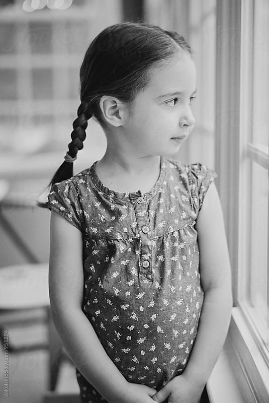 Black and white portrait of a cute young girl in pigtails looking out a window by Jakob for Stocksy United