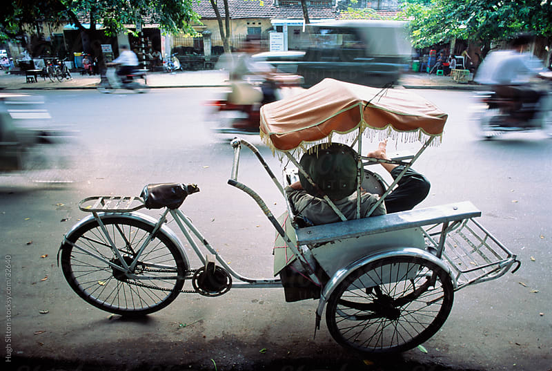 Rickshaw driver taking a break on busy Hanoi street. Vietnam. by Hugh Sitton for Stocksy United