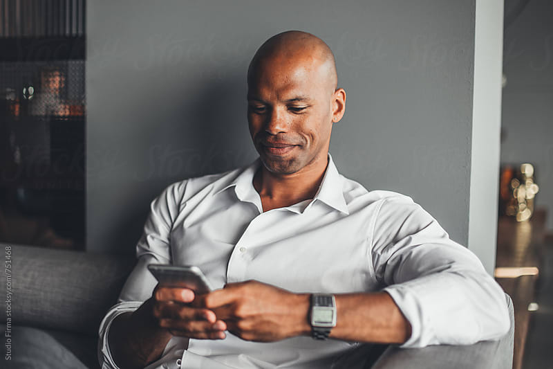 African American Businessman Typing on the Phone by Studio Firma for Stocksy United