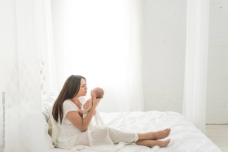 A Beautiful Mother Holds Her Baby In A White Bedroom by Alison Winterroth for Stocksy United