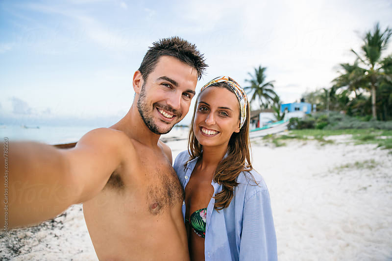 Young happy couple taking a self-portrait on the white sand of the caribbean beach by Alejandro Moreno de Carlos for Stocksy United