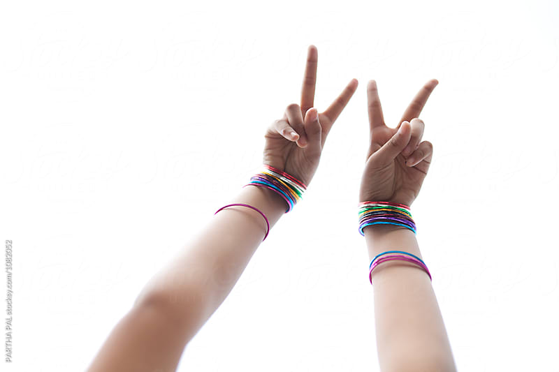 A teenage girl showing V sign by PARTHA PAL for Stocksy United
