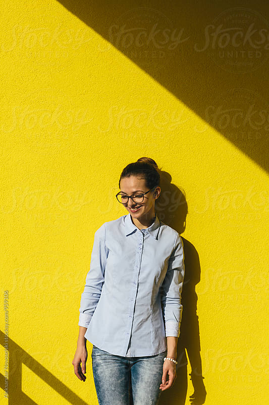Young woman with glasses shot on yellow wall by Aleksandar Novoselski for Stocksy United