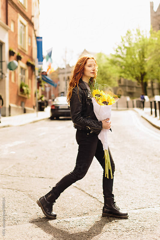 Young Beautiful Girl On the Street Holding Sunflowers by HEX. for Stocksy United