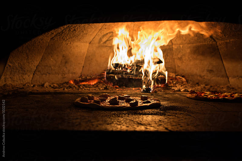 Pizza in brick oven by Andrew Cebulka for Stocksy United