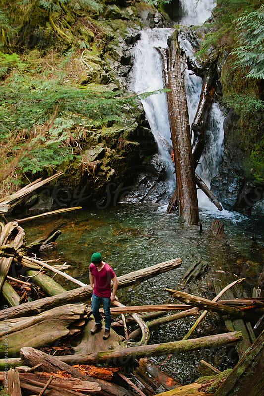 Young man standing next to waterfall by Jesse Morrow for Stocksy United