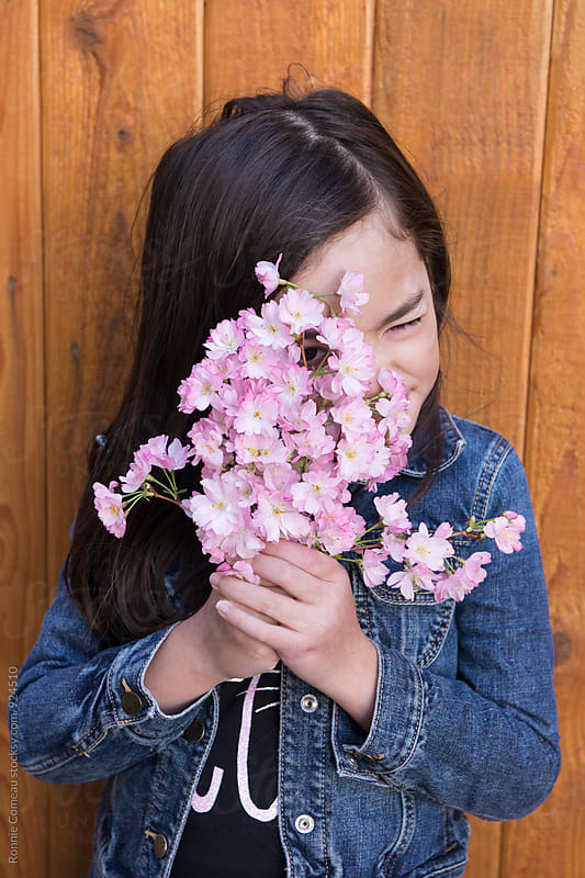 Cute Little Girl Hiding Behind Bouquet Of Flowers by Ronnie Comeau for Stocksy United