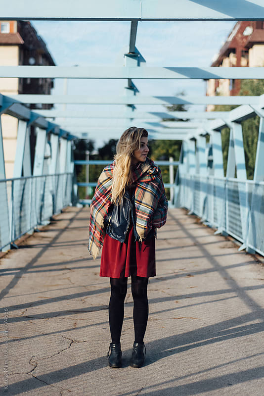 Young stylish woman walking through the bridge by Katarina Simovic for Stocksy United