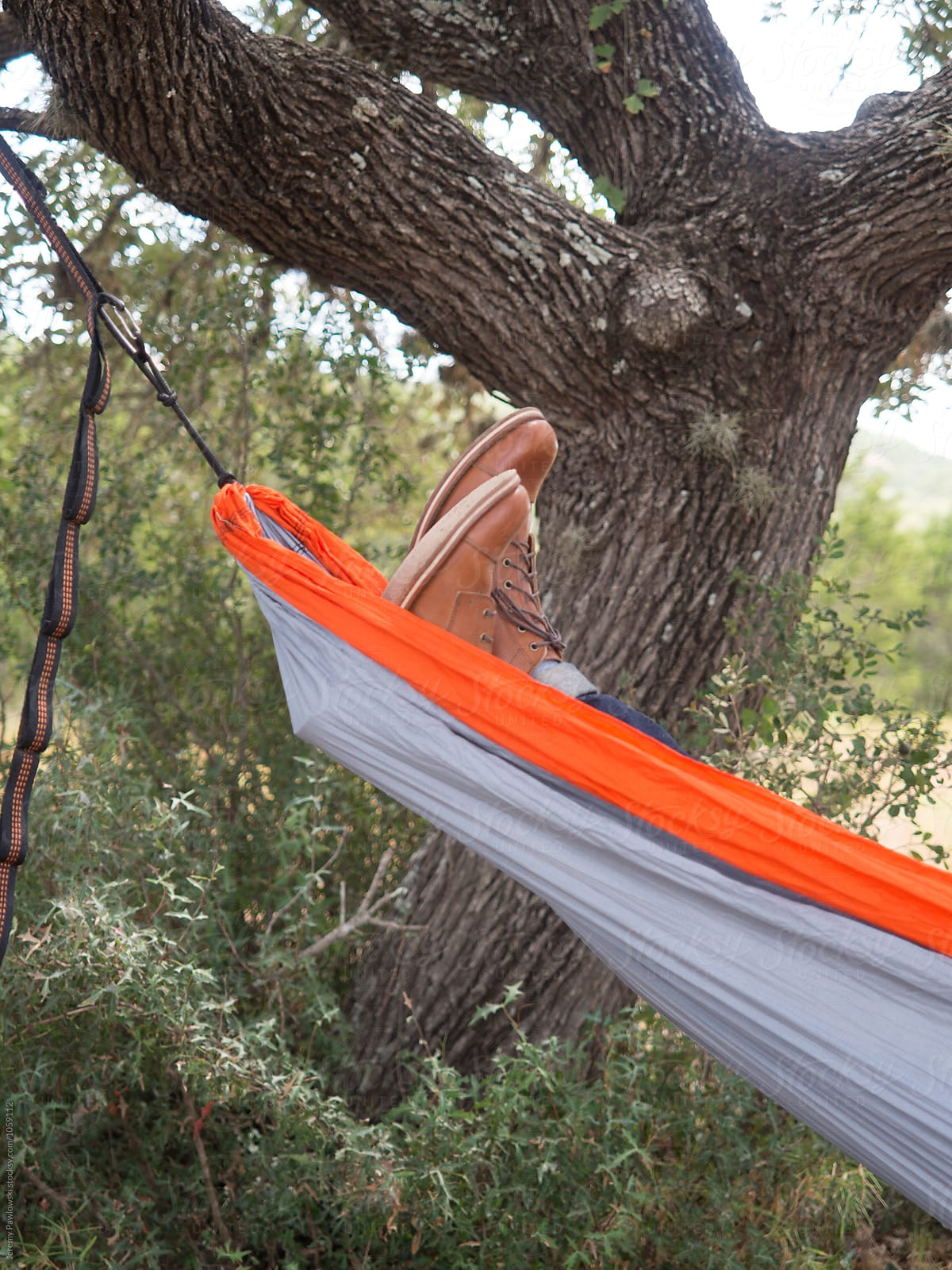 Person In Leather Boots Sleeping In Hammock Hanging In Tree