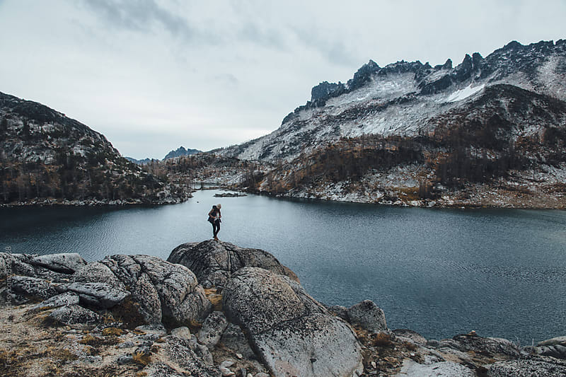 Rugged peaks and blue lake with hiker in foreground by Tari Gunstone for Stocksy United