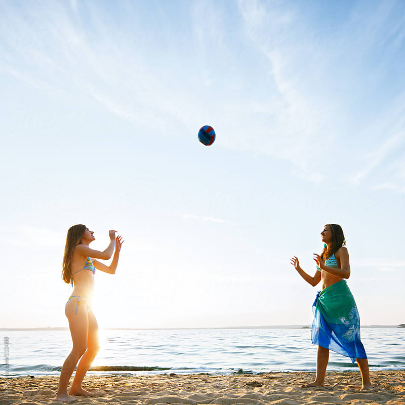 Young women playing beach ball on the beach by Ilya for Stocksy United