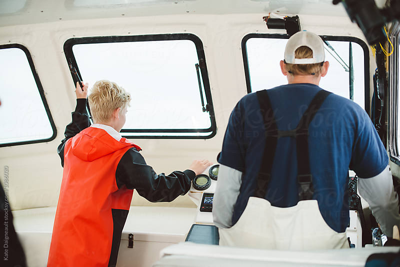 Young fisherman helping his dad captain a commercial fishing boat. by Kate Daigneault for Stocksy United