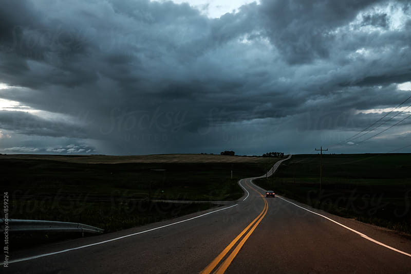 A long car drives toward a storm on a prairie road as dusk. by Riley J.B. for Stocksy United