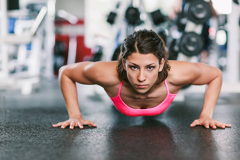 Woman working out doing pushup in the gym  by Suprijono Suharjoto for Stocksy United