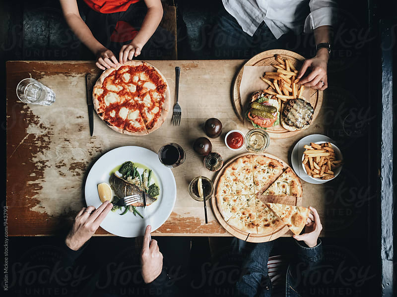 Overhead image of a family eating lunch in a pub by Kirstin Mckee for Stocksy United