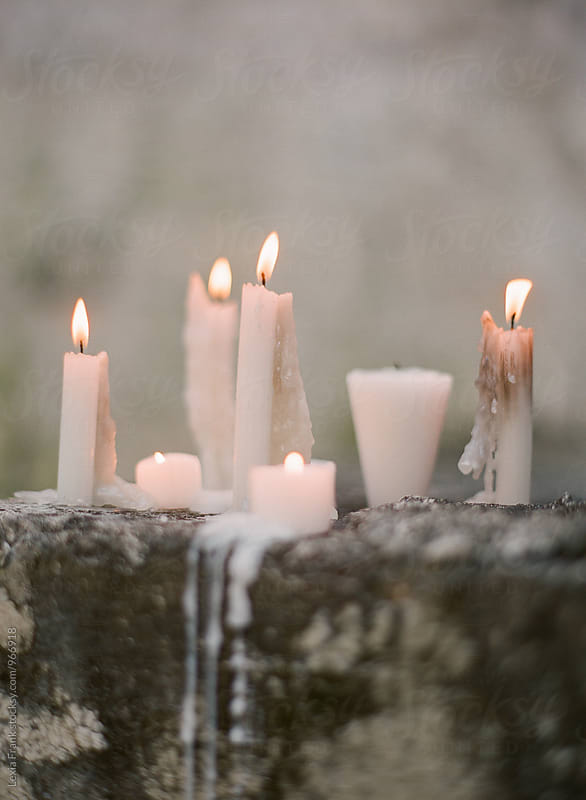 melting candles on old stone by Lexia Frank for Stocksy United
