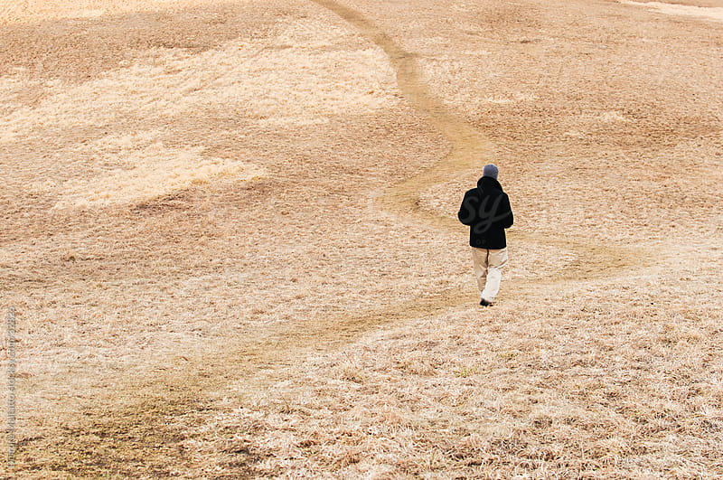 Man Walking Along Path through Field by Deirdre Malfatto for Stocksy United