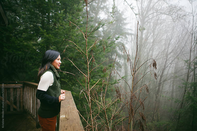 Woman standing outside on a wooden deck with a forest behind her by Kristine Weilert for Stocksy United