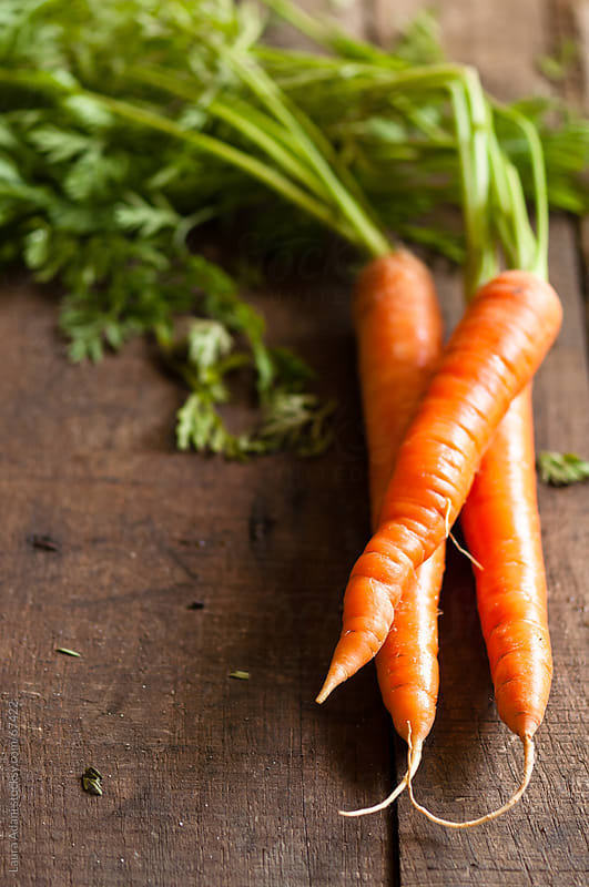 carrots on a wooden background by Laura Adani for Stocksy United