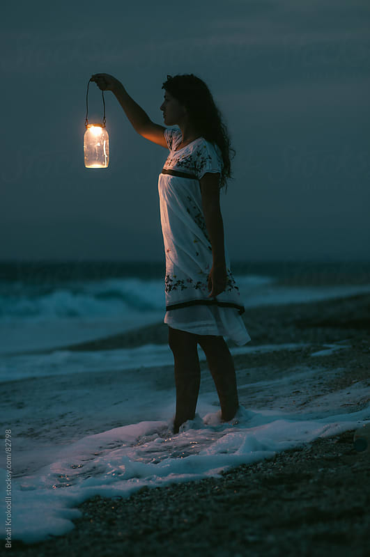 Woman With Lantern on Coast by Branislav Jovanović for Stocksy United