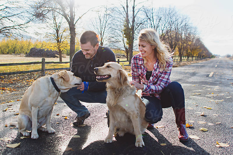 Couple stops to pet dogs  by Tana Teel for Stocksy United