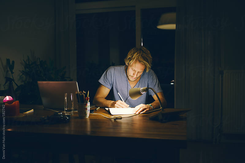 Young blond man working in his home office. by Denni Van Huis for Stocksy United