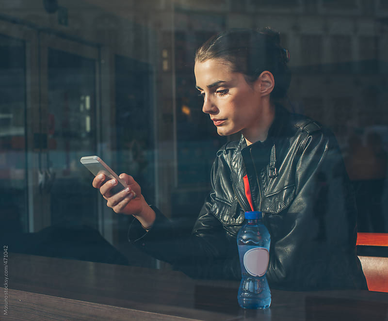 Young Brunette Using Her Smartphone  by Mosuno for Stocksy United