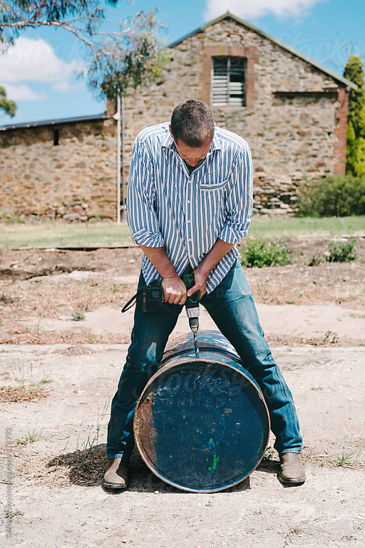 man drilling holes in a 44 gallon drum by Gillian Vann for Stocksy United