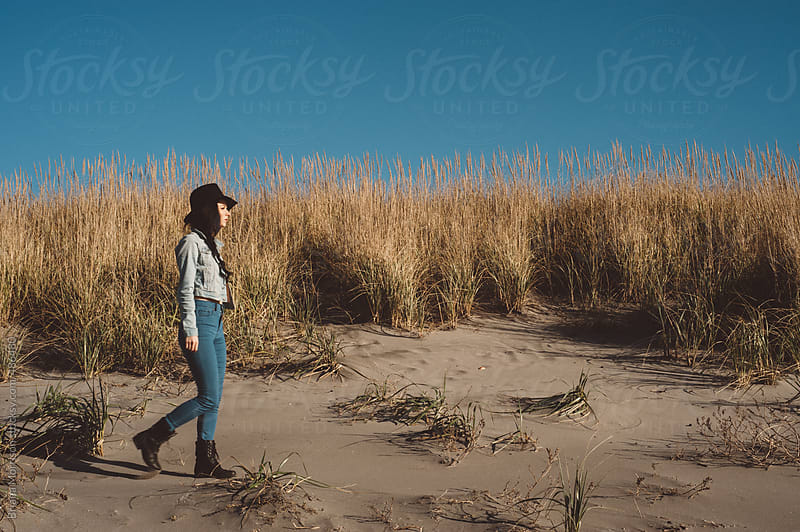 Young Hipster Woman Walking on Sand Dunes by Briana Morrison for Stocksy United