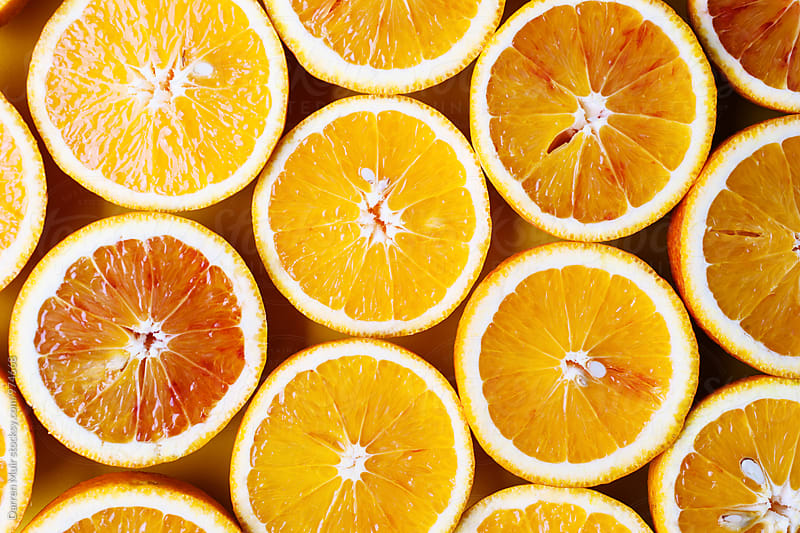 Oranges on a yellow background. Half oranges. by Darren Muir for Stocksy United