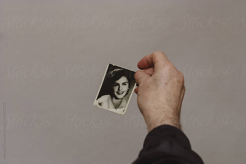 Senior Man Holding 50 Year Old Photo of His Wife  by Nemanja Glumac for Stocksy United